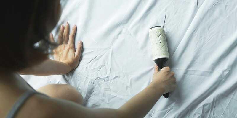 woman using lint roller on bedsheet
